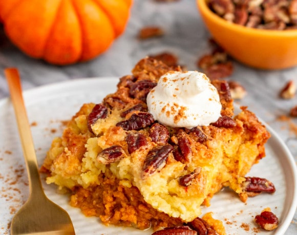 pumpkin dump cake topped with whipped cream and pumpkin spice