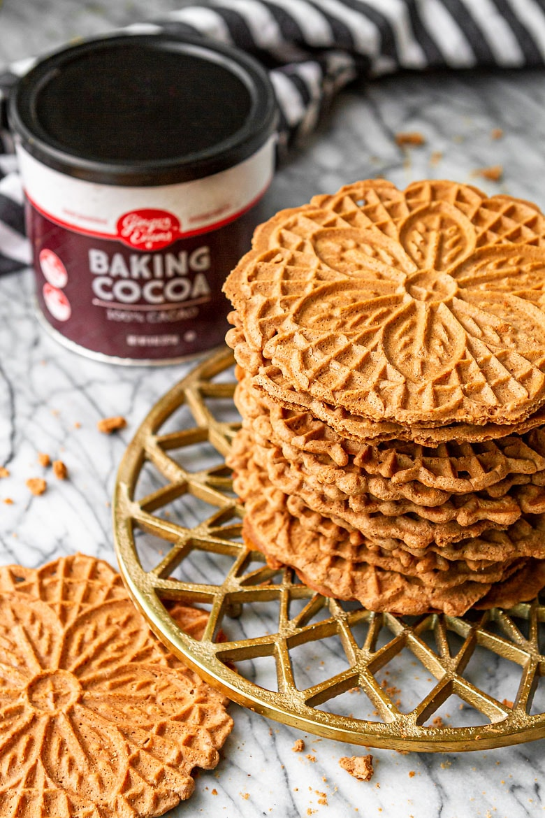 best chocolate pizzelle recipe cookies stacked up with cocoa powder