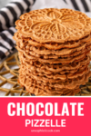 chocolate pizzelle stacked up on a gold trivet with a black & white kitchen towel