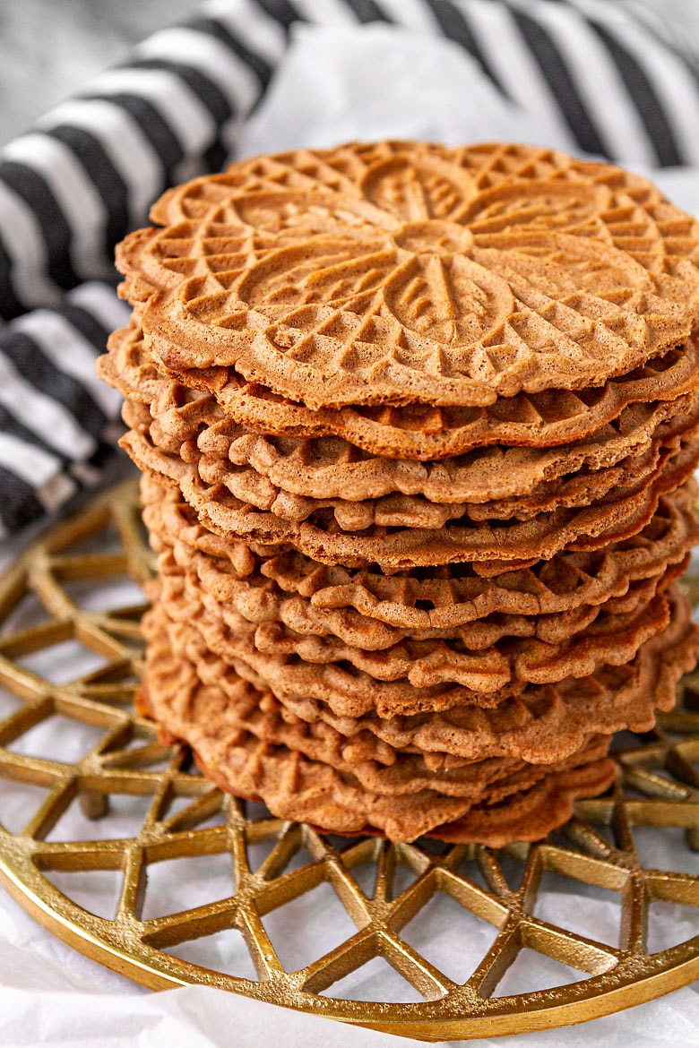 chocolate pizzelle cookies stacked up on a gold trivet