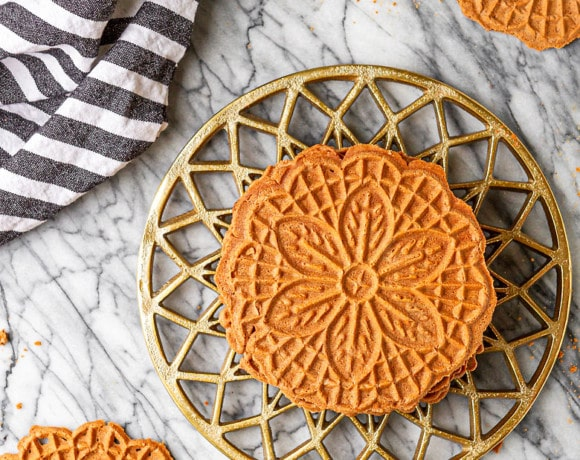 chocolate pizzelle recipe cookies stacked up on a gold trivet