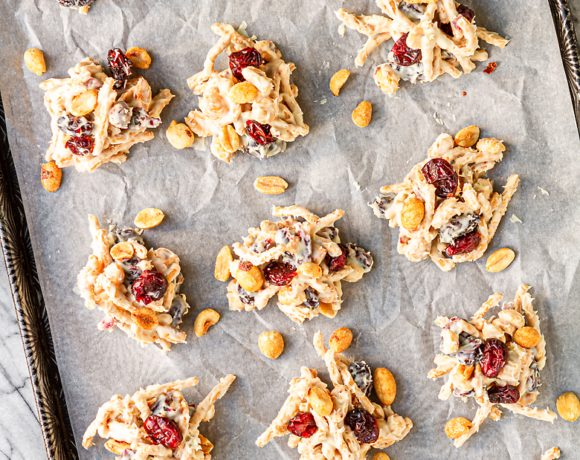 haystack cookies on parchment paper with peanuts and dried cranberries