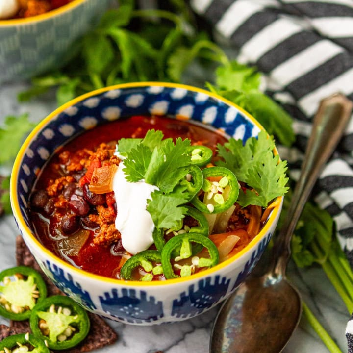 instant pot turkey chili recipe topped with sour cream cilantro and sliced jalapeno peppers