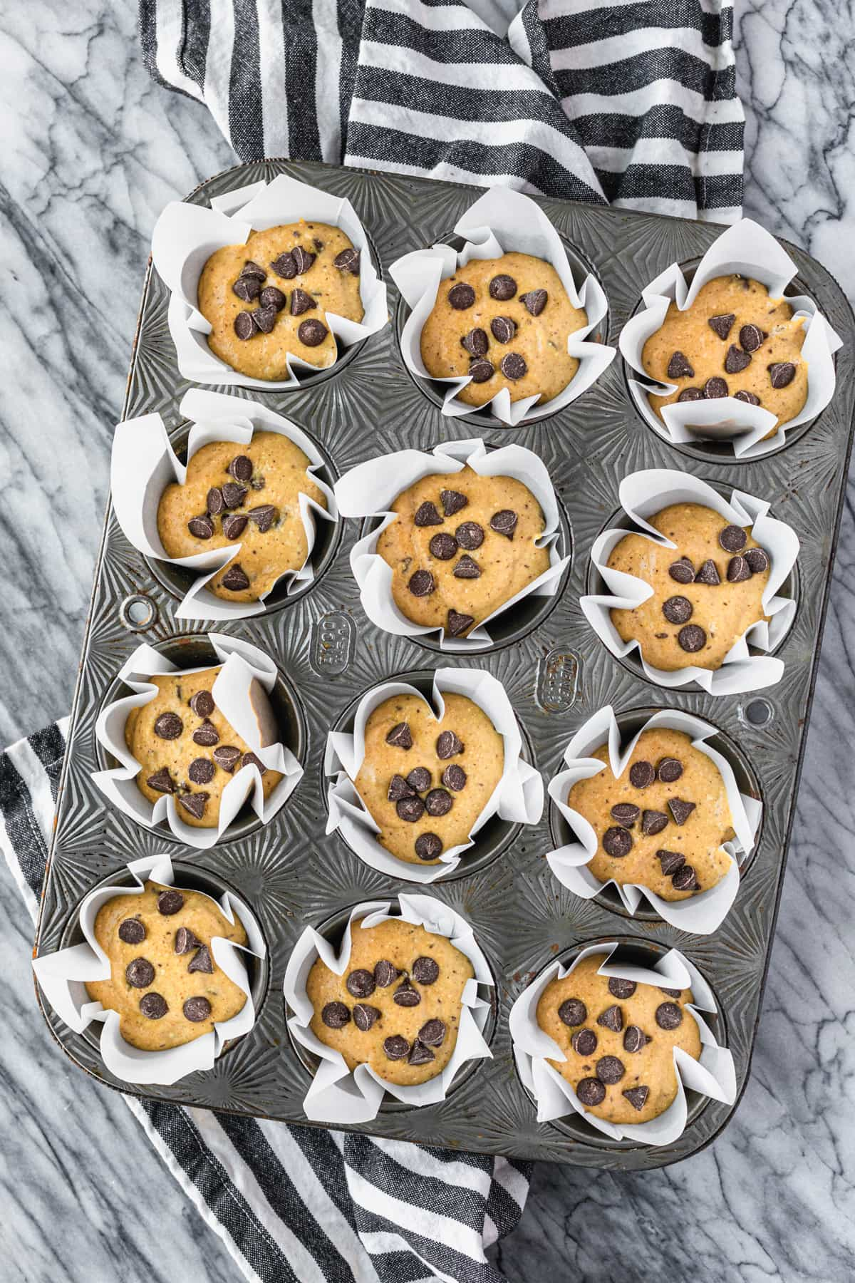 diy tulip cupcake liners in a muffin tin filled with batter
