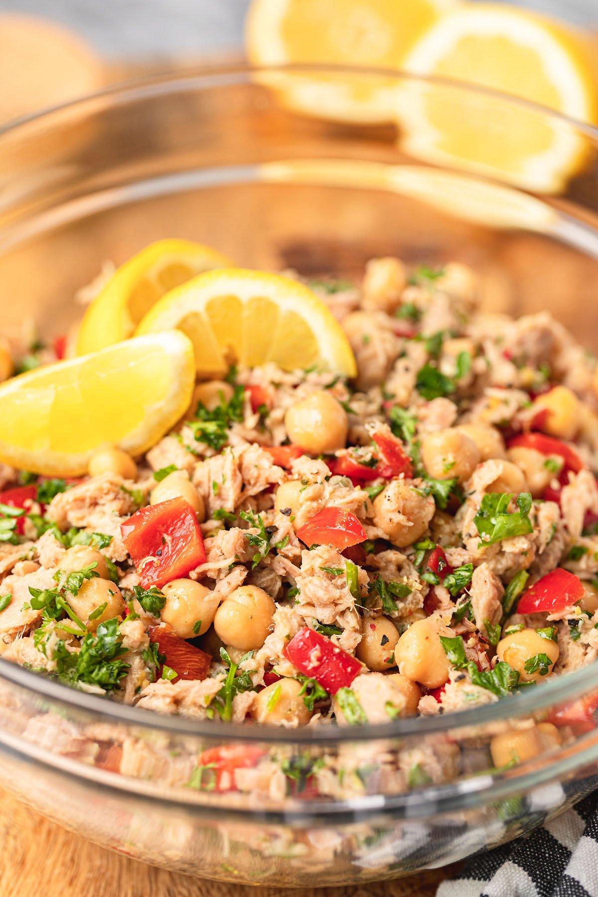 chickpea tuna salad in a glass bowl with lemon garnish