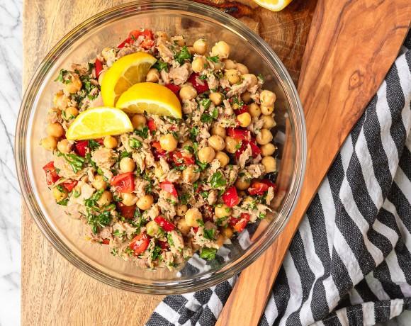 mediterranean tuna salad in a pyrex glass bowl on a wood cutting board