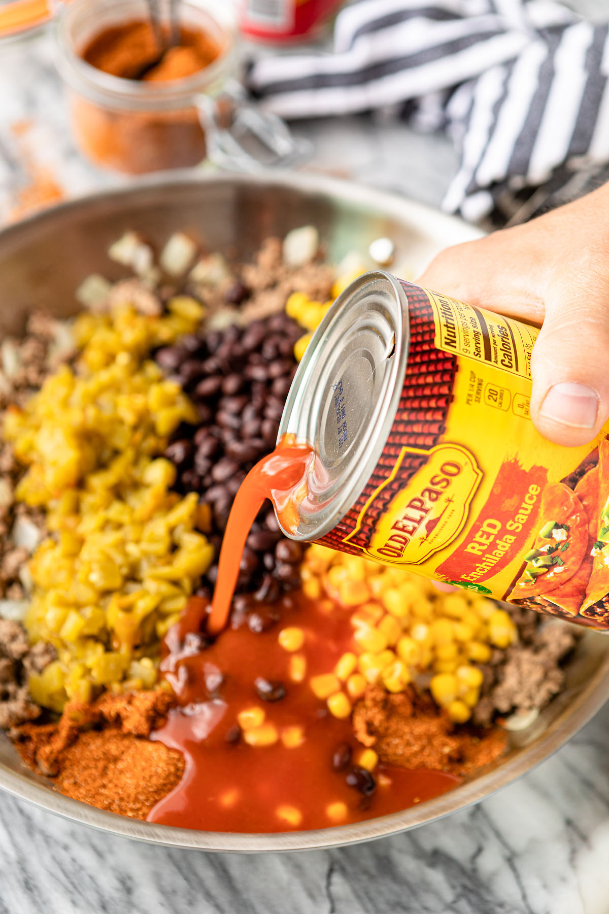 how to make tater tot casserole hand pouring enchilada sauce into ground beef mixture in skillet