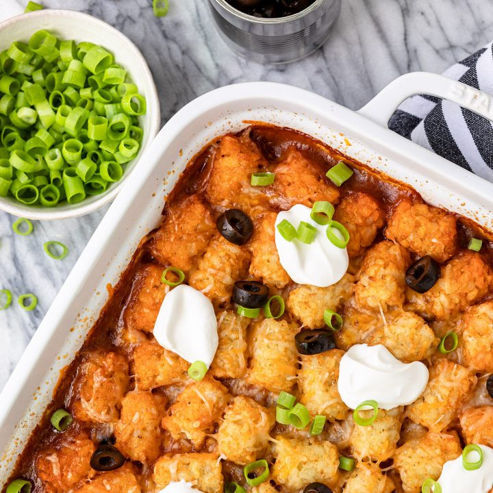taco tater tot casserole recipe in a white ceramic baking dish with sliced green onions and black olives on the side