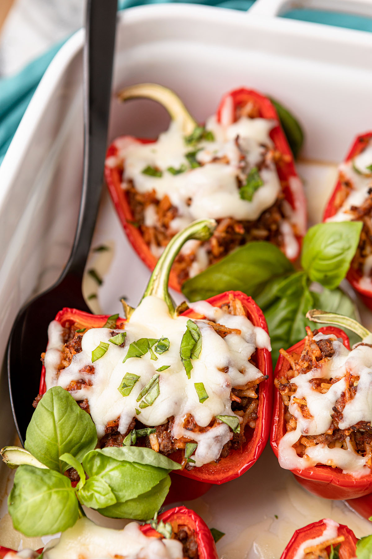 italian stuffed peppers with ground beef and cheese in a white casserole dish with a black serving spoon