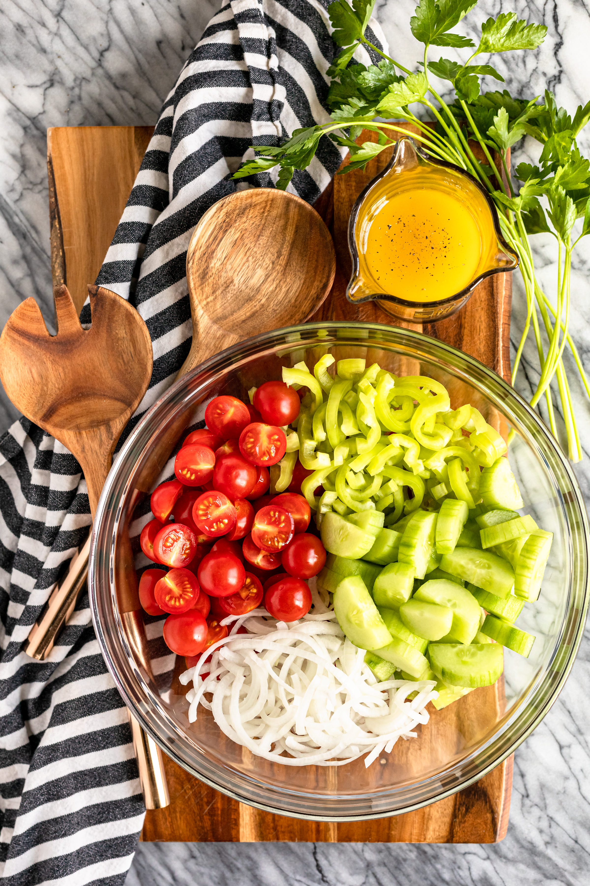 cherry tomato cucumber salad ingredients in a glass mixing bowl with wood salad servers