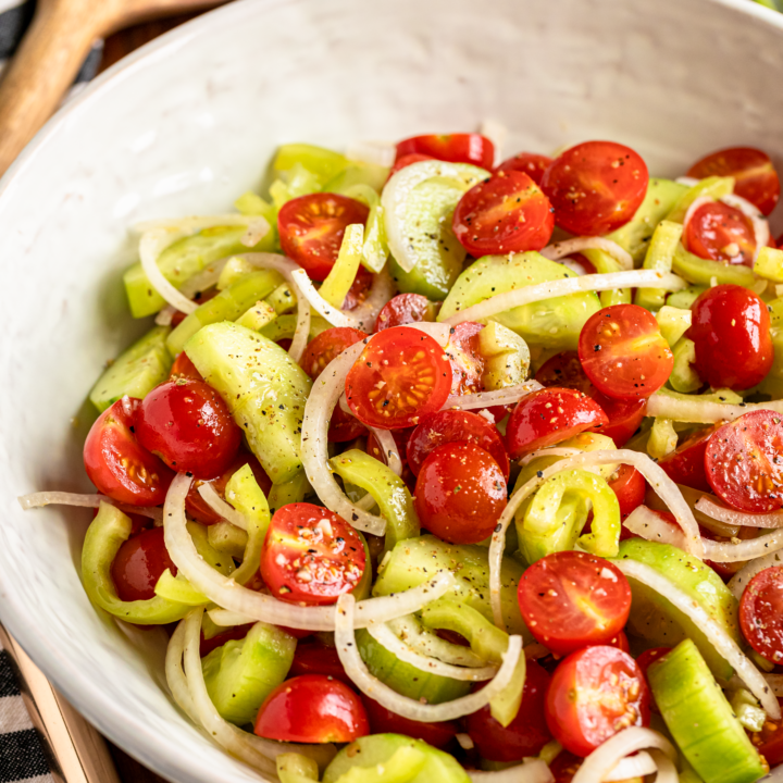 hungarian marinated tomato salad with cucumbers, onions, and wax peppers in a white ceramic serving bowl