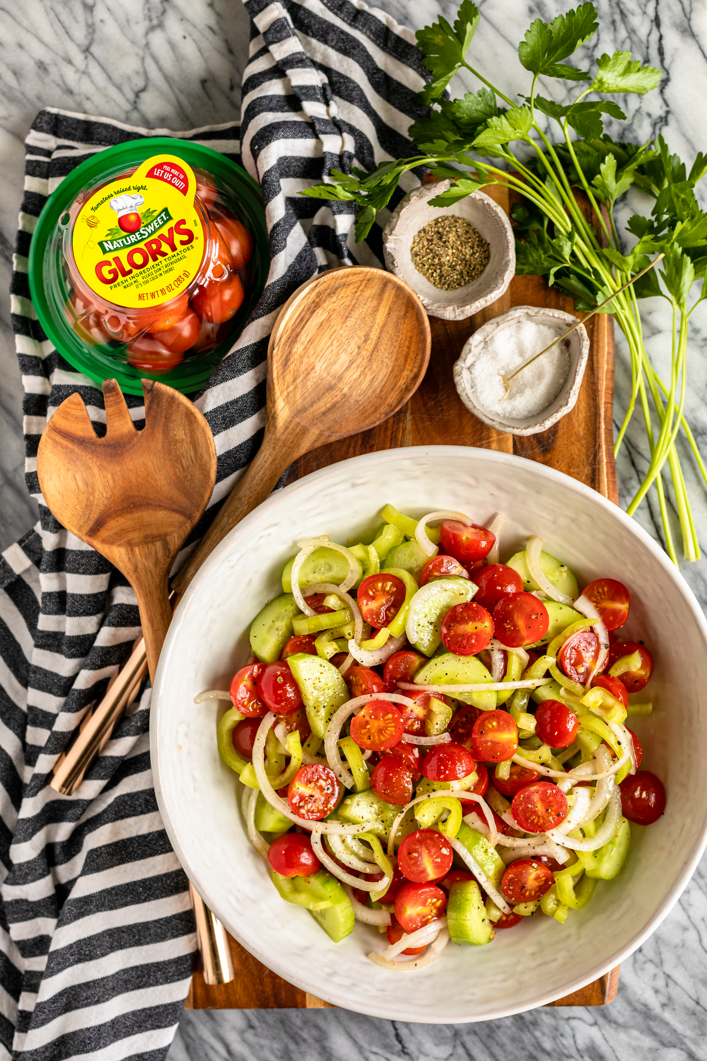 marinated cucumber and tomato salad in a white serving bowl with wood salad servers and a black and white striped kitchen towel