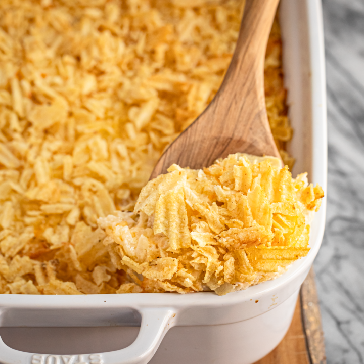 cheesy hashbrown casserole recipe in a white ceramic baking dish with a wooden spoon