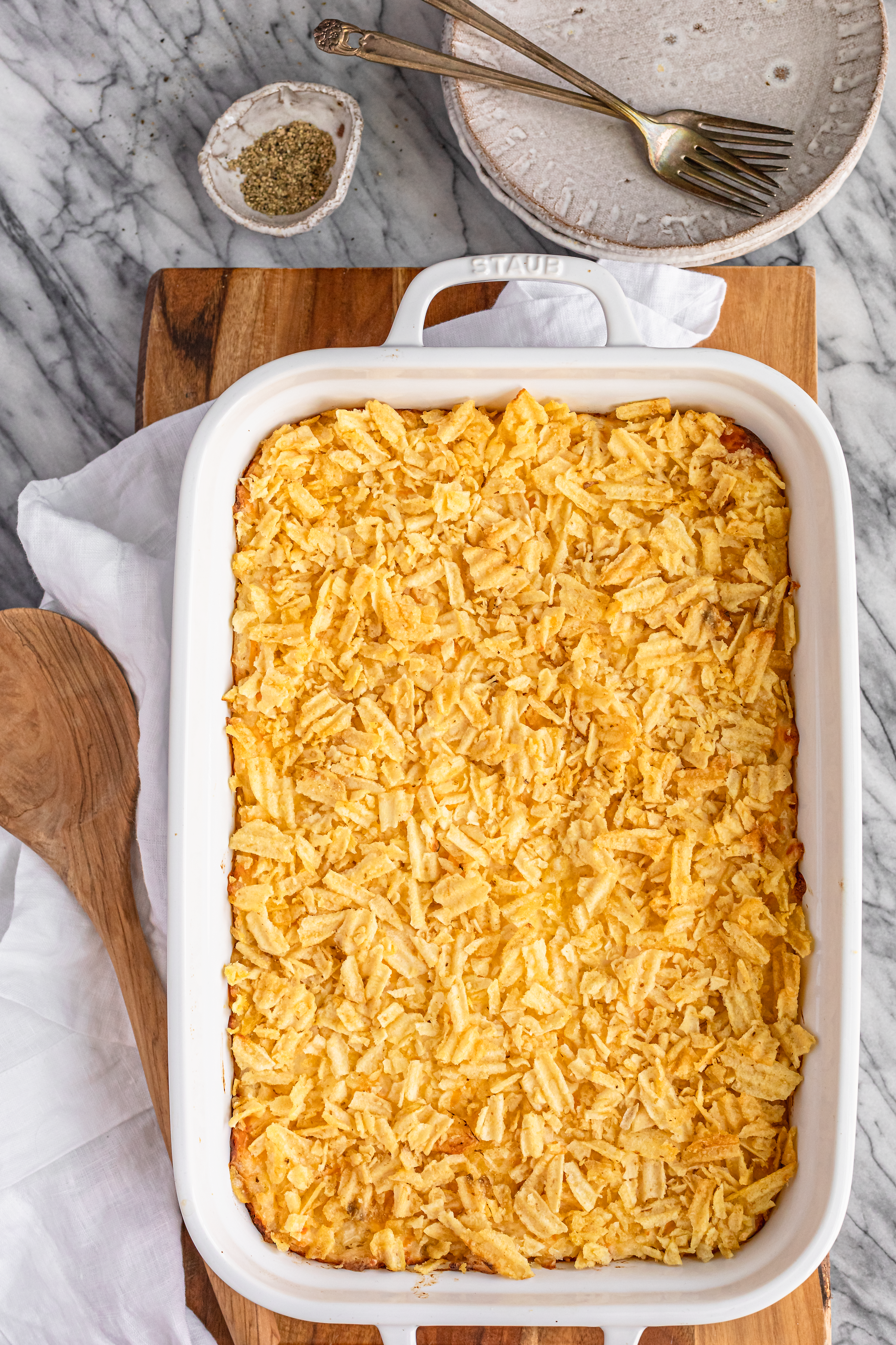 ore ida hash brown casserole topped with crushed potato chips in a white ceramic baking dish on a wooden cutting board