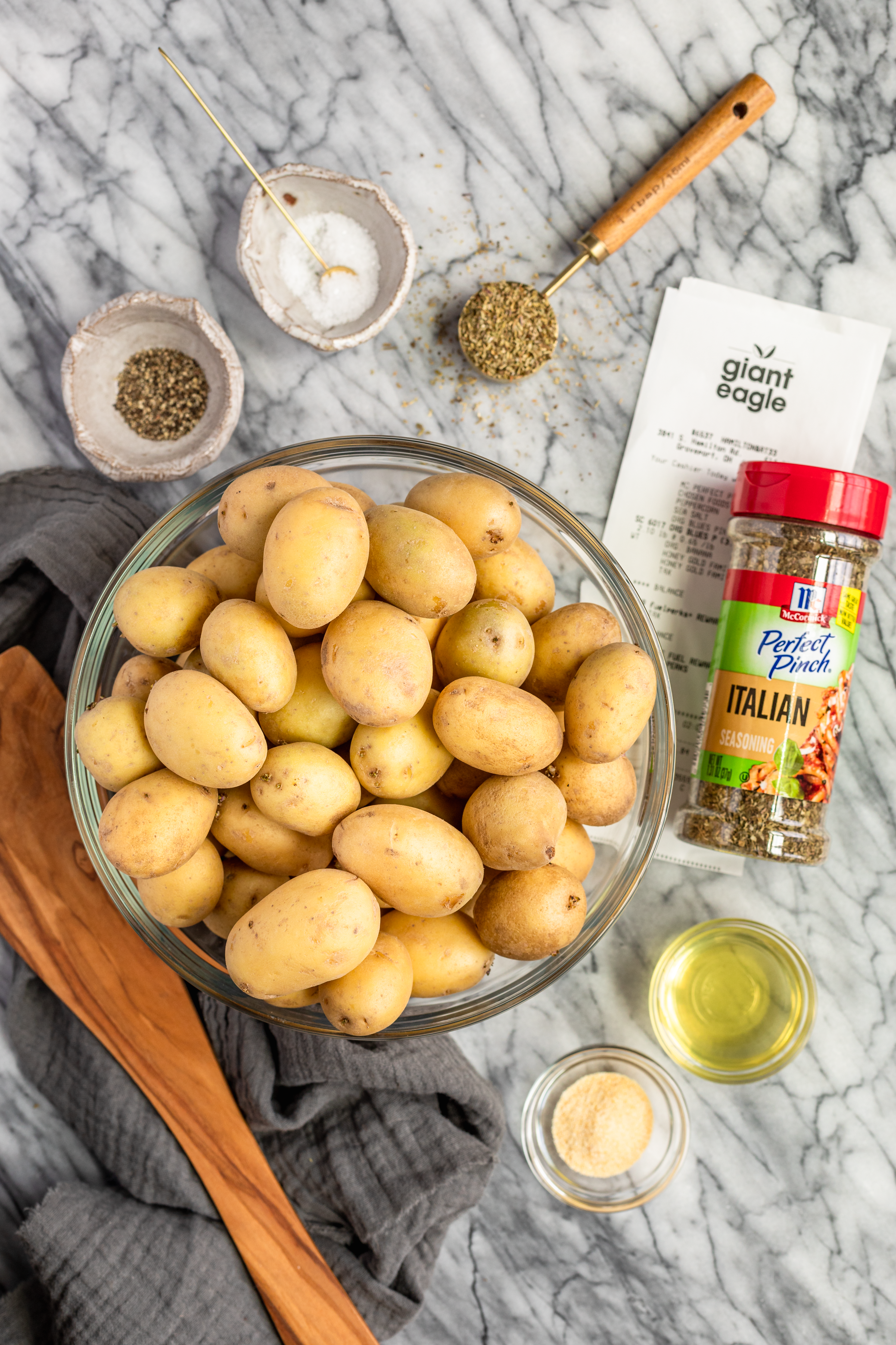ingredients to make Italian garlic baby potatoes on a marble countertop